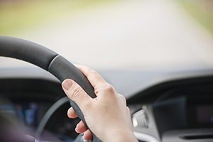 Hand of woman on steering wheel inside car